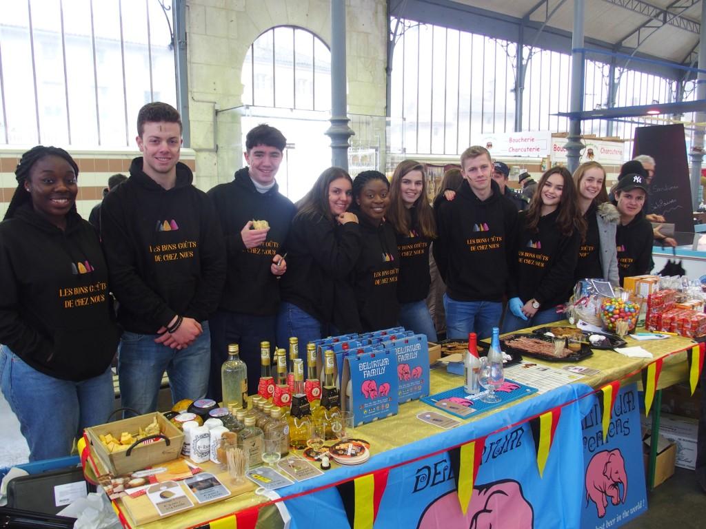 Groepsfoto op de markt bij tafel met streekproducten uit Melle België