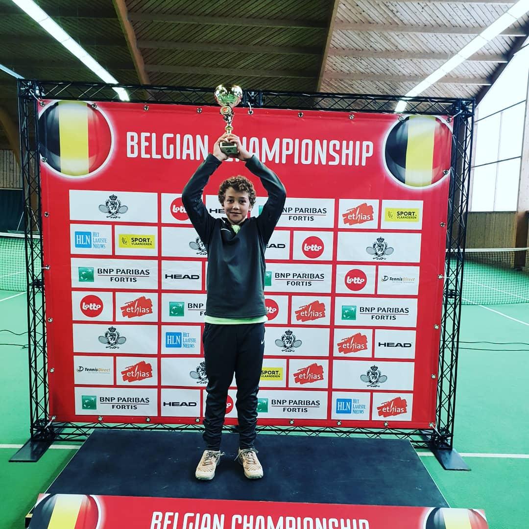 Belgisch kampioen steekt beker omhoog op podium.