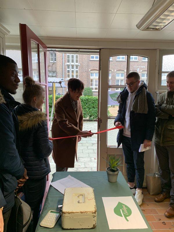 Mevrouw Thienpont knipt een rood lint door voor de opening van de mini-onderneming B-WAY.