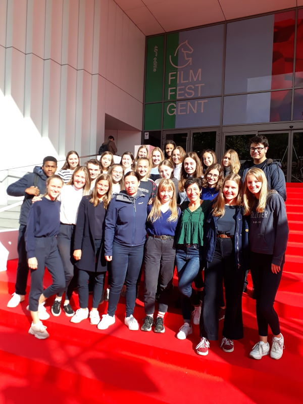 Leerlingen en leerkracht van het seminarie Spaans staan op de rode loper aan de ingang van Kinepolis Gent.