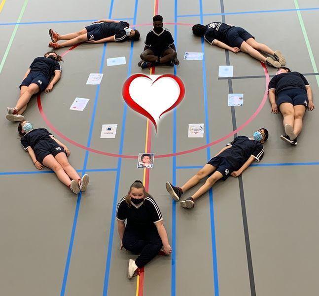 Leerlingen liggen op de grond en vormen met hun lichaam een hart