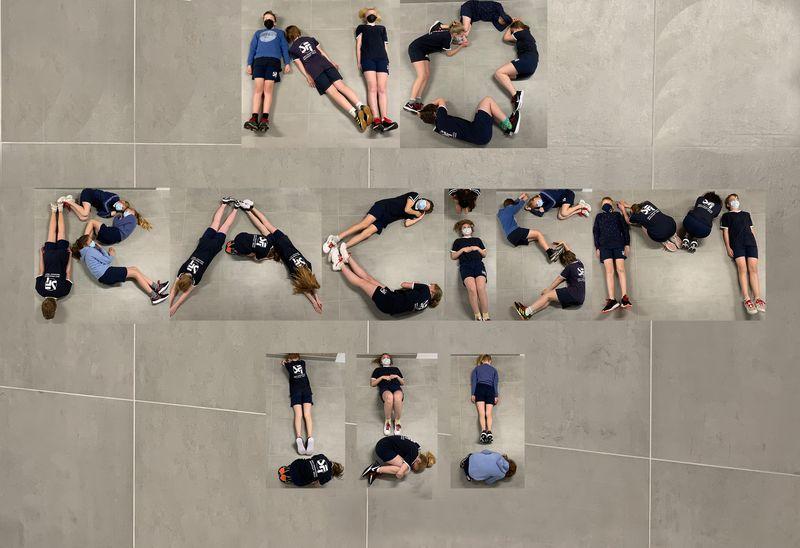 Leerlingen liggen op de grond en vormen met hun lichamen de woorden No Racism!!!