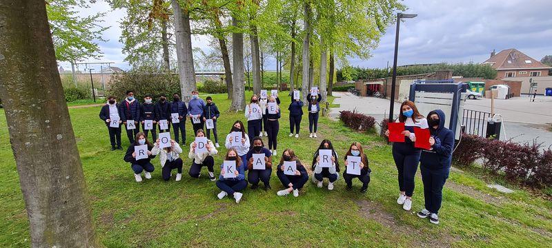 Een groep leerlingen waarbij ieder een blad met een letter op voor zich houdt. 'Geef racisme de rode kaart'