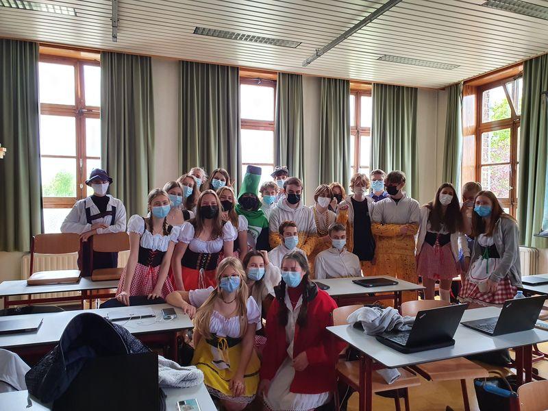 Leerlingen gekleed in het thema Oktoberfest poseren in groep voor de foto in een klaslokaal.
